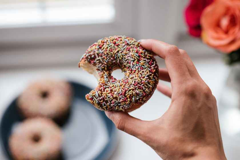 person holding doughnut with sprinkles